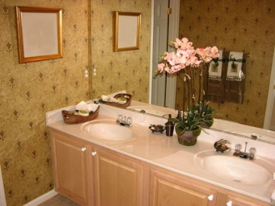 a neutral refined bathroom with wallpaper and a pretty pink orchid on the vanity to make it more chic and luxurious