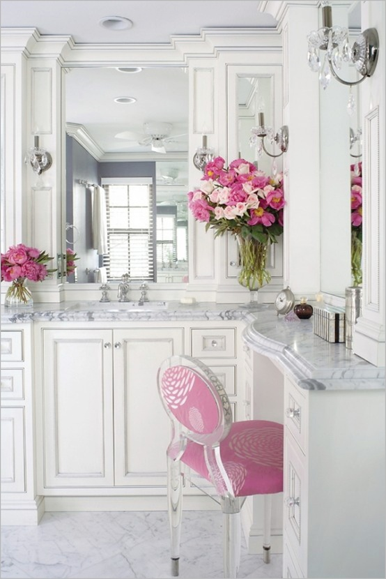 bold pink blooms in vases and a matching chair in pink refresh and spice up the bathroom done in white and neutrals