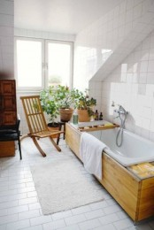 a neutral and serene bathroom with a wood clad tub and some wooden furniture plus potted greenery and blooms