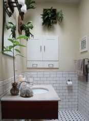 a neutral bathroom with wall planters and a plant on the sink to refresh this space and make it lively and cool