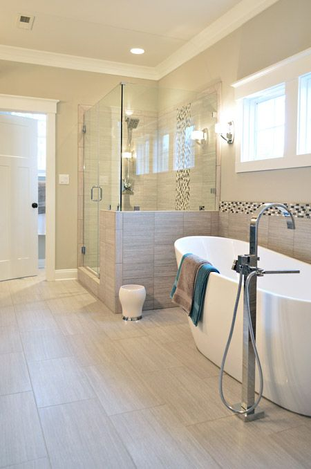 a stylish modern bathroom clad with sandy tiles, with a shower space with half walls and a lovely bathtub is filled with light