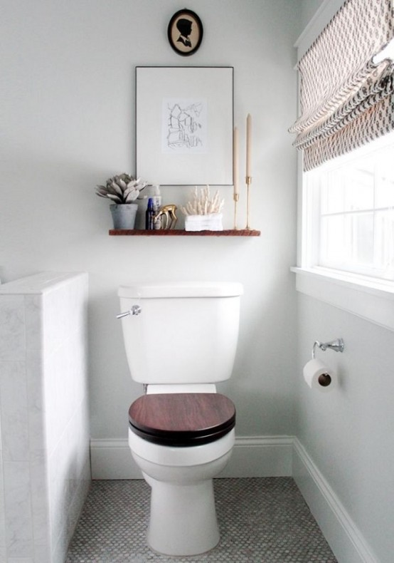 a small neutral bathroom with a half wall that divides the toilet from the rest of the space and neutral shades