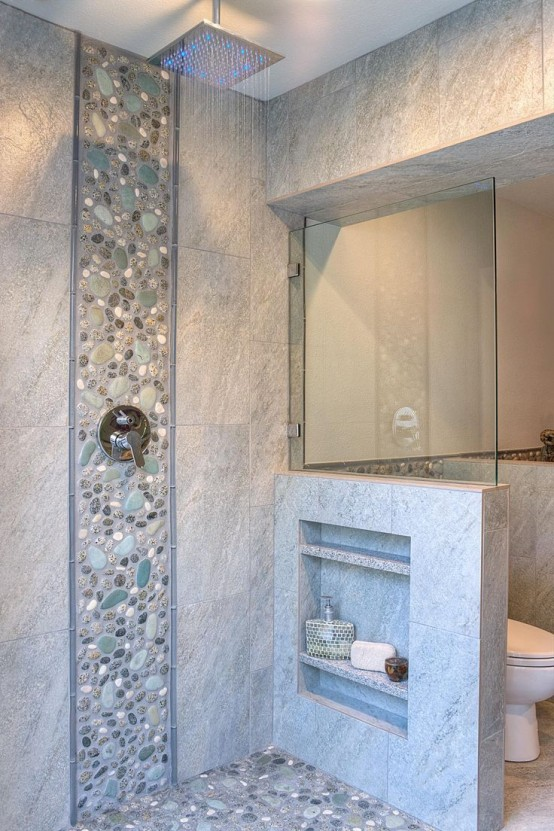 a neutral bathroom clad with tiles and faux pebbles, with a pony wall that had some shelves integrated is a lovely space