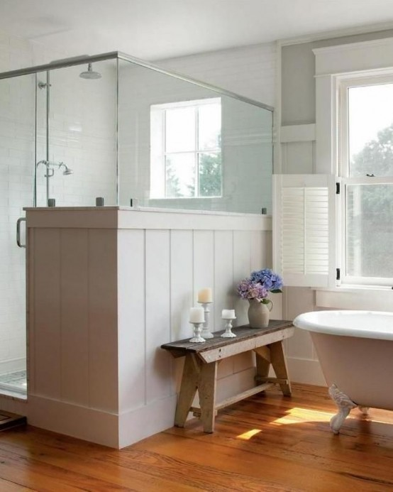 a neutral farmhouse bathroom with planked walls and a shower space, with a pony wall and a vintage bathtub plus a bench