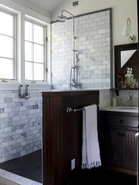 an elegant bathroom clad with marble subway tiles, with a dark half wall and a matching vintage vanity looks chic