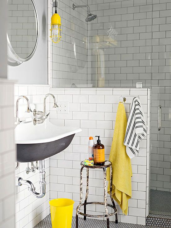 a mid-century modern bathroom clad with white subway tiles, with a half wall, a vintage sink and touches of yellow for a brighter look