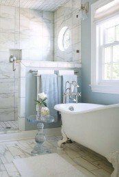 a beautiful bathroom with blue walls and a shower space clad with marble tiles, with a vintage bathtub and a pony wall in the shower space