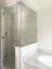 a neutral bathroom with a small shower space clad with tiles, a pony wall and a glass partition, a built-in sink in the vanity