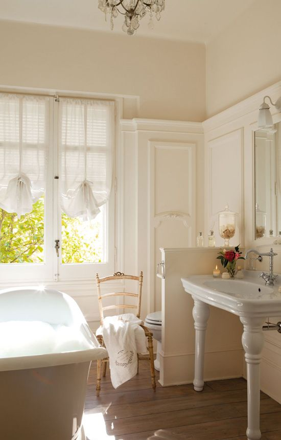 a neutral vintage bathroom with a vintage tub, a half wall that separates the toilet zone from the rest of the space, vintage curtains and furniture
