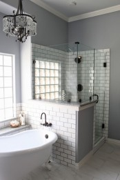 a grey bathroom with white subway tiles, shower space with a half wall, a crystal chandelier and a vintage bathtub