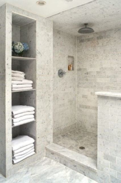 a neutral contemporary bathroom clad with white marble tiles, with a half wall for the shower space and built in shelves