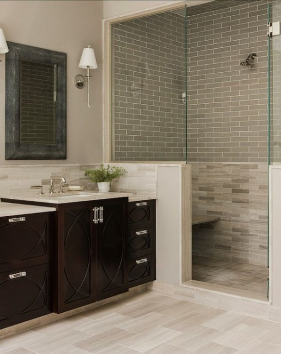 a neutral farmhouse bathroom with a half wall and grey tiles in the shower, a dark stained vanity and a large mirror