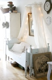 a neutral shabby chic kid's room with a pastel blue bed, white furniture, a canopy with lights and some vintage decor
