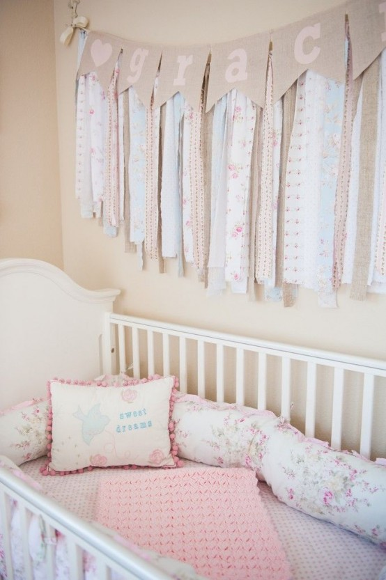 a shabby chic nursery with warm-colored walls, a white crib, pink and floral bedding and a tassel garland over the bed