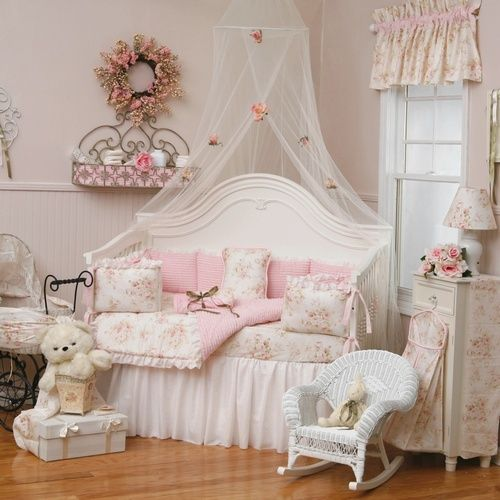 a pink and white shabby chic kid's room with white furniture, floral bedding and curtains, pink touches and cute toys
