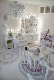 a white shabby chic bedroom with refined white furniture, a pink play kitchen and a crystal chandelier and lights