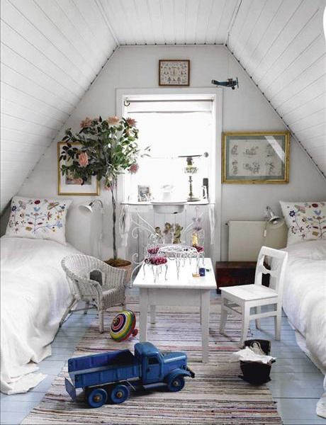 a white shabby chic attic bedroom with floral pillows, a gallery wall, a statement plant, white furniture, a striped rug and toys