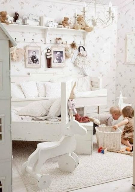 a white shabby chic kid's room with white furniture and a chandelier, floral wallpaper, a shelf with toys and baskets for storage