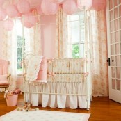 a shabby chic kid's room with pink walls, pink paper lamps, floral bedding and textiles
