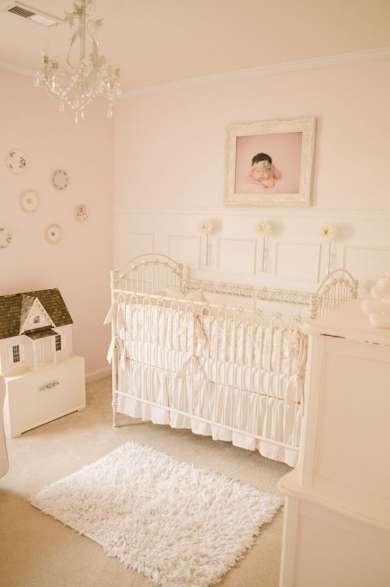 a neutral and blush nursery with vintage furniture, a gallery wall with decorative plates, a crystal chandelier, an artwork