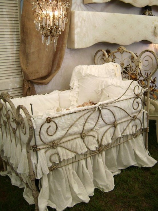 a pastel shabby chic kid's room with lavender walls, a metal crib with white bedding and a crystal chandelier