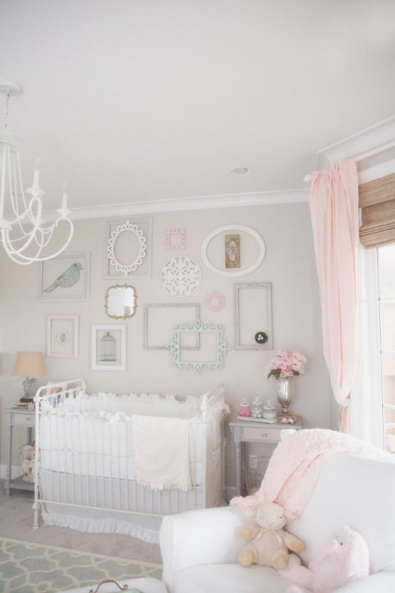 a pastel shabby chic bedroom with dove grey walls, a gallery wall of mirrors and empty frames, a white chandelier and pink textiles is very elegant