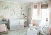a shabby chic nursery with dove grey walls, pink textiles and pink touches, a gallery wall of empty frames and elegant furniture