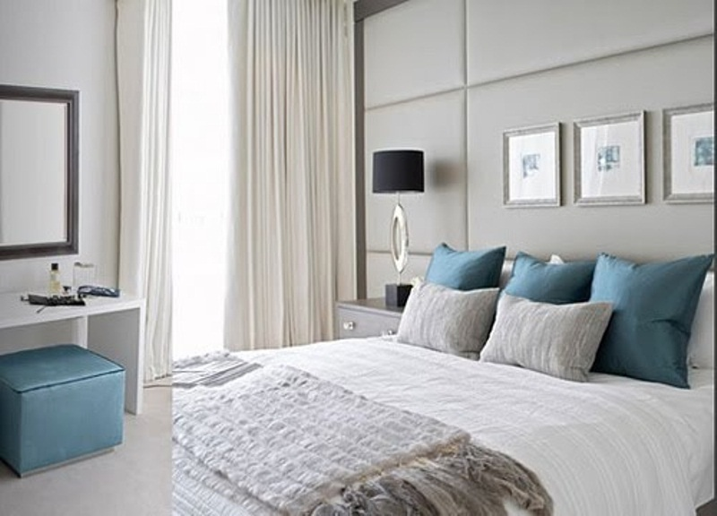 a light grey bedroom with bold blue pillows and a little ottoman to add color