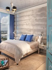 a light grey and silver bedroom infused with bold blue – pillows and curtains of this shade