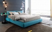 a contemporary bedroom with a graphite grey statement wall, a grey floor and rugs, a turquoise bed and grey bedding