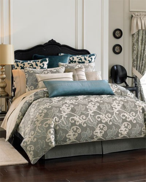 a creamy bedroom with a navy velvet bed, grey and blue bedding with prints