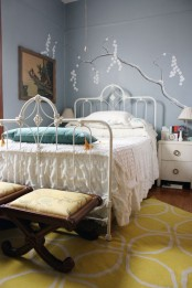 a grey bedroom spruced up with a bold blue pillow and some mustard touches