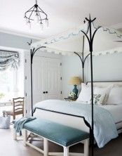 a light blue and creamy bedroom with touches of black for more drama