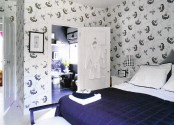 a dark blue, creamy and white bedroom wiht a grey bed and bold bedding