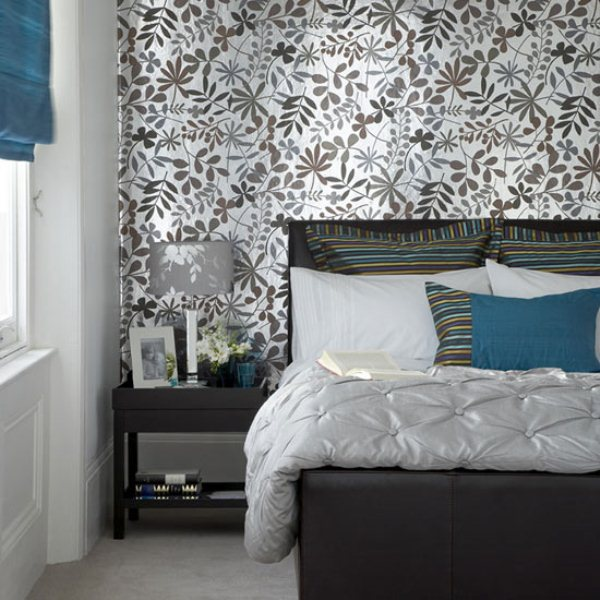 a grey and silver bedroom with touches of bold blue is a very refined space