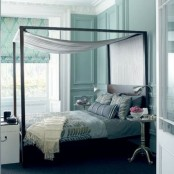 a tiffany blue bedroom with a bed done with grey and silver bedding and a silver canopy