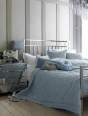 a grey bedroom with a silver finish bed, a mirror nightstand and blue and grey bedding