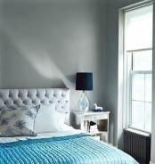 a light grey bedroom, a grey upholstered bed and a turquoise blanket plus navy lamps