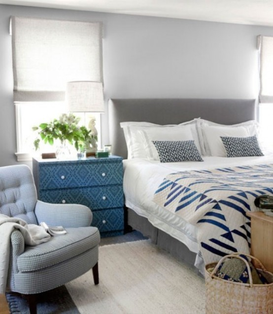 a bedroom in the shades of light grey, a bold patterned sideboard and grey and blue bedding