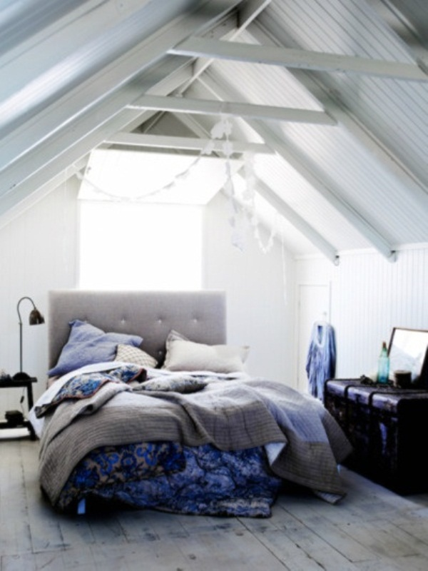 a light grey and creamy attic bedroom with a grey upholstered bed and grey and blue bedding