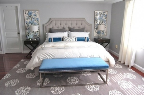 a light grey bedroom spruced up with bold blue pillows, a bench and artworks