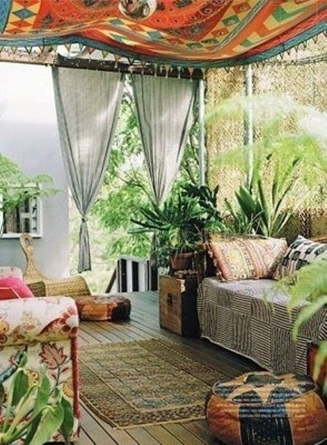 a bright boho patio done with boho rpitned furniture, rugs and a canopy plus lots of potte greenery and plants
