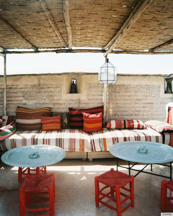a welcoming boho patio done with blue and reds, with lots of stripes and candle lanterns