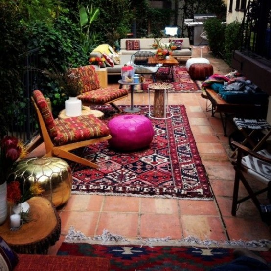 a colorful boho patio done with rugs, printed furniture, pillows, ottomans, a gold ottoman and potted plants