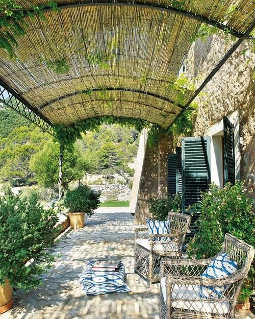 a relaxed Spanish patio with wicker chairs, potted greenery and blue printed pillows