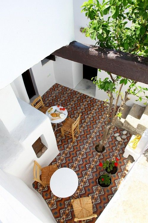 a boho patio with a mosaic floor, wooden furniture, potted blooms and greenery and a pizza stove