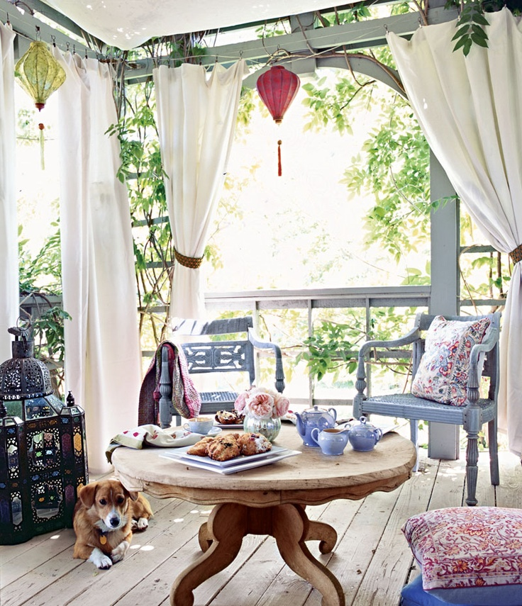 a boho patio with colorful paper lanterns and an oversized mosaic lantern, floral pillows and light blue furniture