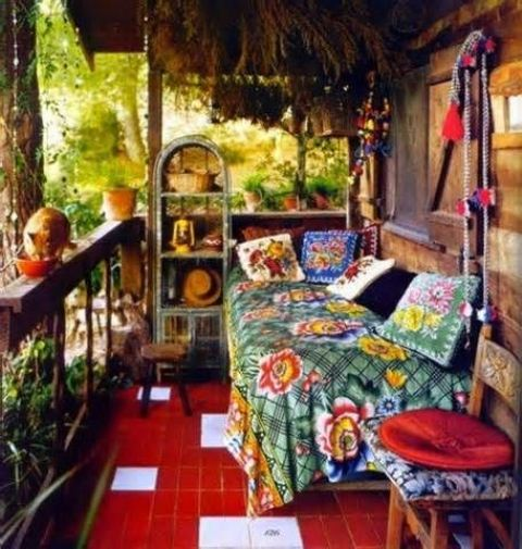 a very colorful boho patio with a daybed, a shelving unit, bright textiles and potted greenery