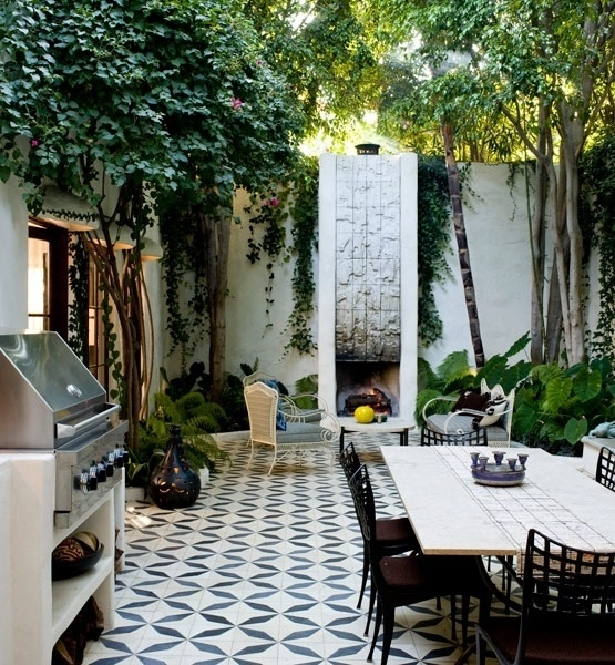 an eclectic patio with a mosaic tile floor, wood and metal furniture, a fireplace and a hearth for cooking