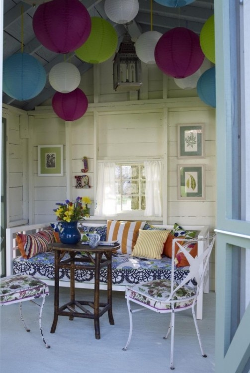 a patio done with colorful paper lanterns, white furniture with floral upholstery, colorful pillows and blooms